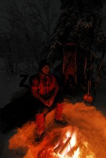 Mann sitzt am Lagerfeuer