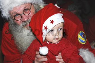 lachender Weihnachtsmann haelt Kind im Arm, Gaellivare