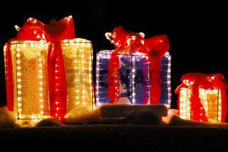 beleuchtete Geschenkpakete im Schnee