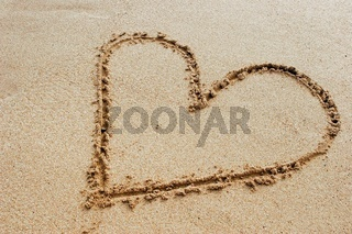 Sign of a heart drawn in the sand with a sea wave