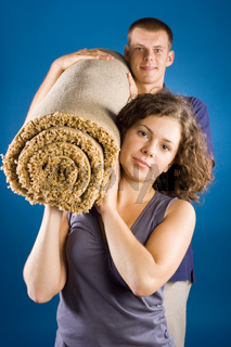 man and woman with rolled carpet