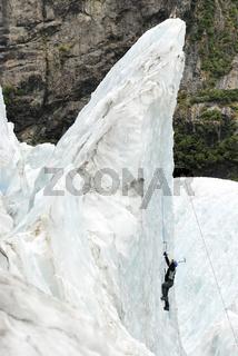 Eisklettrerin an einer Eiswand im Gletscherbruch des Franz-Josef-Gletschers