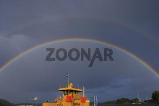 Regenbogen nach einem Gewitter über einer Fähre in Schweden bei Stegeborg