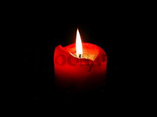 Brennende rote Kerze, Licht in der Dunkelheit