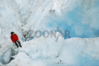 Frau steht neben einer blauschimmernden Gletscherspalte