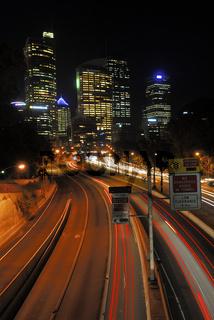 Lichtspuren von Autos auf einer Schnellstrasse und Hochhaeuser; Sydney