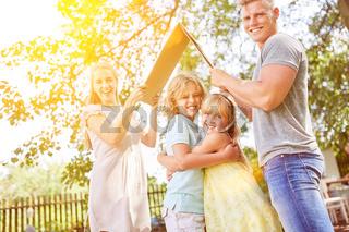 Eltern halten Dach über Kinder als Sicherheit