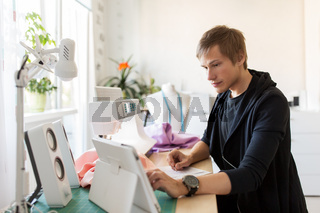 fashion designer with tablet pc working at studio