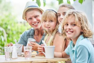 Familie sitzt entspannt am Kaffeetisch im Garten