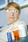 Elderly woman with pill bottles
