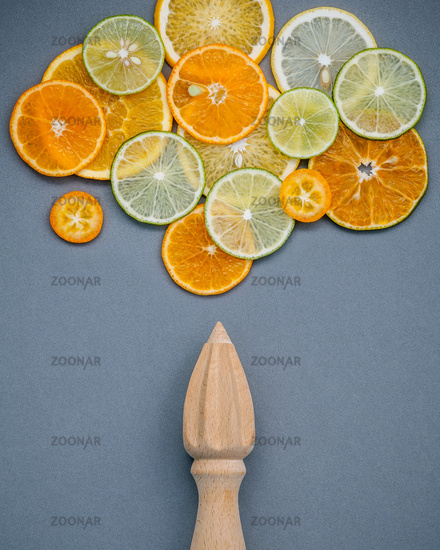 Mixed fresh citrus fruits and wooden juicer for summer citrus juice. Fresh citrus fruits sliced lime,orange and lemon on dark gray background flat lay.