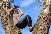 Woman in tree looking through binoculars