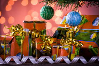 Christmas gifts with blurred lights on background and ribbon under the tree