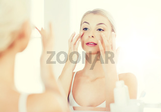 happy woman applying cream to face at bathroom