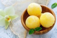 Balls of melon sorbet in a wooden bowl.