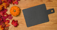 Autumn foliage with a pumpkin and an empty blackboard