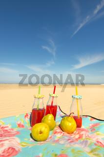 Bottles lemonade and fruit at beach