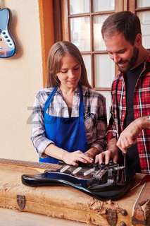 Gitarrenbauer und Lehrling reparieren E-Gitarre