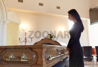 sad woman with coffin at funeral in church