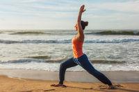 Woman doing yoga asana Virabhadrasana 1 Warrior Pose on beach on