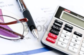 Tax calculator pen and glasses