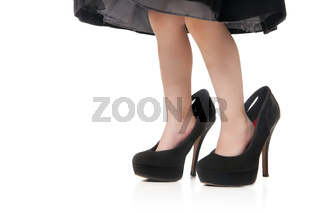 Childs feet in a big black shoes with heels