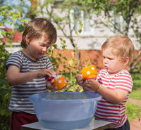 Children washing dishes outdoors