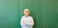 Alte Frau als Lehrer vor Tafel in Schule