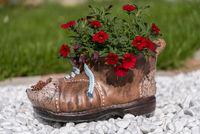 Keramikschuh mit roten Blumen auf weissem Zierkies
