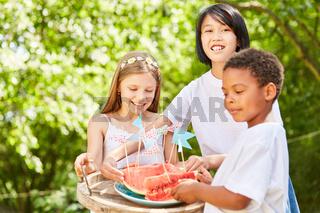 Gruppe Kinder verteilt eine Wassermelone