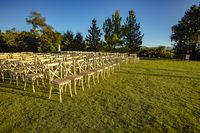 Chairs set up on a lawn for a wedding cerimony with no people yet from the front