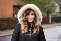 smiling young woman wearing winter coat with fake fur hood