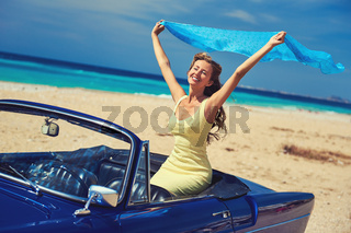 Happy woman with a hands raised sitting in retro cabriolet car on the beach near the turquoise sea