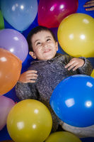 childhood, Brunette boy playing with a lot of colorful balloons, smiles and joy at birthday party
