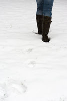 female legs in boots walking through fresh snow