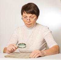 Eye problem. Woman with glasses and a magnifying glass reading a newspaper