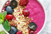 Red smoothie bowl with beets and black grapes.