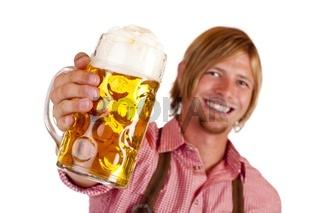Glücklich lachender Mann mit Lederhose hält Oktoberfest Maß Bier