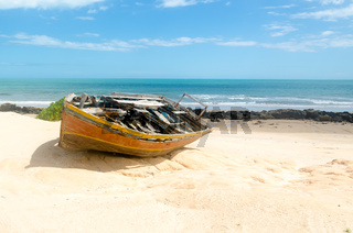 Front view of a broken canoe over the sand
