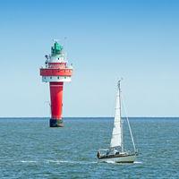 Roter Leuchtturm und Segelboot in der Wesermündung