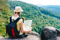 Young hipster tourist girl holding and looking map on trip; lifestyle concept adventure, traveler with backpack on background mountain landscape horizon