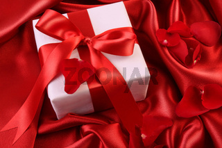 Red ribbon holiday gift on satin