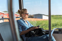 Portrait of woman driving on moving bus sitting by window using mobile phone.