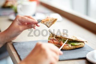 woman eating salmon panini sandwich at restaurant
