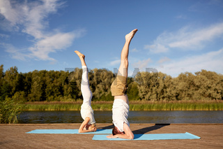 couple making yoga headstand on mat outdoors