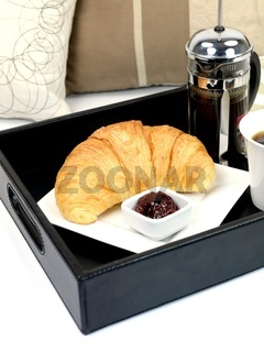 A breakfast tray with fresh coffee and a croissant