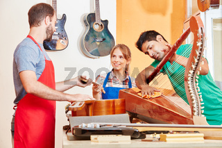 Gitarrenbauer und Lehrlinge in Teamwork
