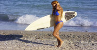 Sexy muscular young woman surfer with her board