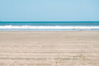 beach sand closeup with ocean wave and blue sky background -
