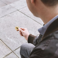 young man holding bitcoin coin in his hand